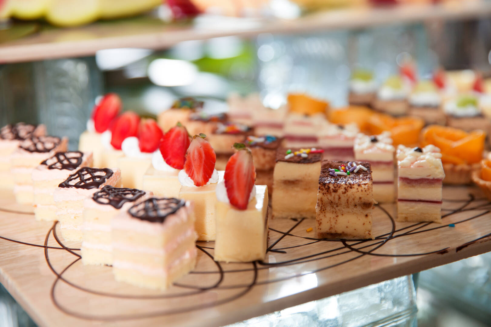 Delicious mini cakes with cream, chocolate and strawberries on buffet table. Catering concept